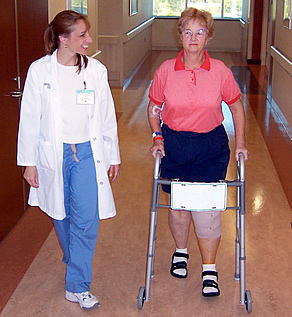 Patient using walker after knee replacement surgery