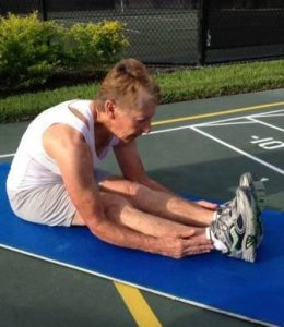 Betty Plum stretching on mat after hip replacement surgery by Dr. Robert Zehr